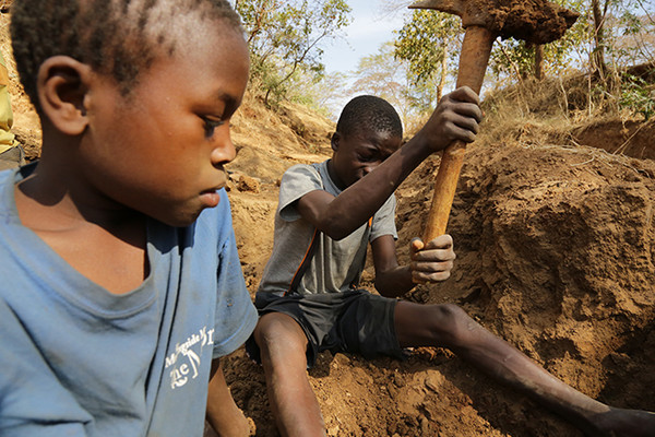 Two 13 year old boys digging for gold in a mine in Mbeya region, Tanzania. (c) 2013